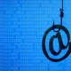 Phishing hook symbolizes social engineering.